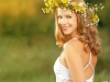 beautiful woman in wreath of flowers lies in the green grass out