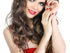 Beautiful model with red lips, nails and shiny volume curly hair