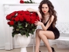 Sexy beautiful woman with red roses bouquet in interior apartmen